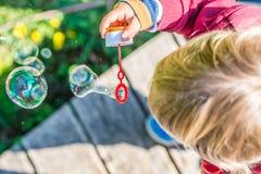 年轻白肤金发的儿童吹的泡影 免版税库存照片