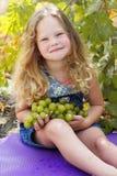 白肤金发的儿童女孩用葡萄在秋天葡萄园里 库存图片