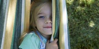 白肤金发的儿童女孩画象,放松在一个五颜六色的吊床 免版税库存图片