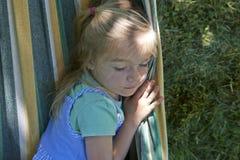 白肤金发的儿童女孩画象,放松在一个五颜六色的吊床 库存图片