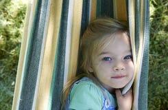 白肤金发的儿童女孩画象,放松在一个五颜六色的吊床 免版税库存照片