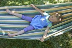 白肤金发的儿童女孩画象,放松在一个五颜六色的吊床 图库摄影