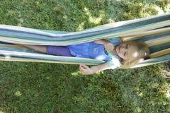 白肤金发的儿童女孩画象,放松在一个五颜六色的吊床 免版税图库摄影