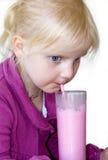 白肤金发的儿童饮用的奶昔 免版税库存照片