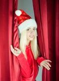 白肤金发的克劳斯窗帘女孩开张圣诞&# 免版税库存图片