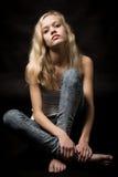 白肤金发的十几岁的女孩坐演播室地板 图库摄影