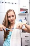 白肤金发的十几岁的女孩掠过的牙 库存照片