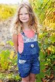 白肤金发的卷曲儿童女孩在葡萄庭院里 免版税库存图片