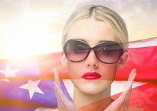 白肤金发的反对美国国旗的妇女佩带的太阳镜在背景中 免版税库存照片