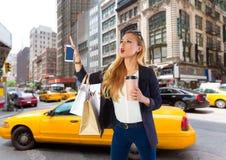 白肤金发的叫购物旅游的女孩一辆黄色出租汽车NYC 免版税库存照片