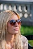 白肤金发的可爱的妇女佩带的太阳镜 免版税库存照片