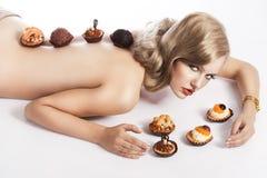 白肤金发的吃的女孩查找性感的酥皮点心 免版税图库摄影