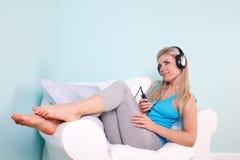 白肤金发的听的音乐坐对妇女 库存照片
