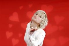 白肤金发的吹的亲吻妇女 免版税库存照片