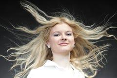 白肤金发的吹的头发她的妇女 免版税库存照片