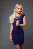 白肤金发的喝马蒂尼鸡尾酒的女孩佩带的晚礼服 免版税库存照片