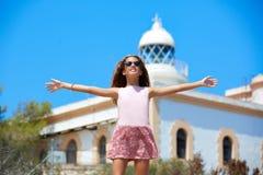 白肤金发的在地中海灯塔的女孩开放手 免版税库存照片