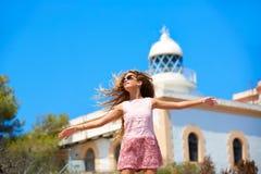 白肤金发的在地中海灯塔的女孩开放手 库存图片