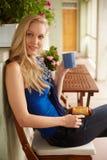 年轻白肤金发的在大阳台的妇女饮用的茶 库存照片