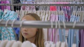 白肤金发的在挂衣架的女孩贴合在精品店的衣裳和购物 股票视频