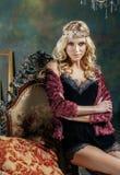年轻白肤金发的在神仙的豪华内部的妇女佩带的冠与空的古董构筑总财富,不可思议的富有的概念 库存照片