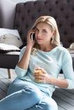白肤金发的夫人拿着汁液玻璃和谈话每个电话 图库摄影