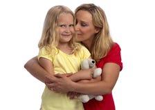 白肤金发的女儿愉快的拥抱的母亲 免版税库存照片