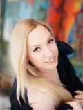 白肤金发的女孩一半恳切地转动了微笑的五颜六色的背景 免版税库存图片