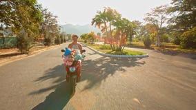 白肤金发的女孩乘坐沿空的街道的摩托车 股票录像