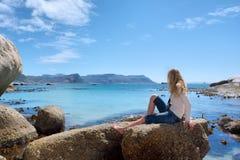 白肤金发的女孩享用在多岩石的海滩的太阳 免版税库存照片