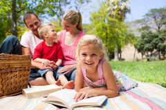 白肤金发的女孩位于的野餐读取桌布 免版税库存图片
