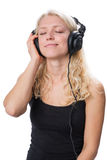 年轻白肤金发的女孩佩带的耳机和享用音乐 库存照片