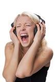 年轻白肤金发的女孩佩带的耳机,尖叫 图库摄影