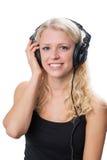 年轻白肤金发的女孩佩带的耳机 免版税图库摄影