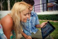 白肤金发的女孩和浅黑肤色的男人人调查Ipad 免版税库存照片
