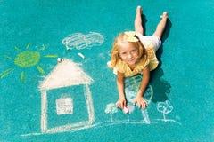 白肤金发的女孩和用粉笔写的图画 免版税库存照片