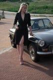 白肤金发的女孩和老黑汽车 免版税库存图片