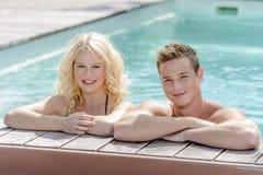 白肤金发的女孩和英俊的男孩水池的 免版税库存照片