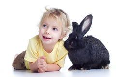 白肤金发的女孩和黑色兔子 免版税图库摄影