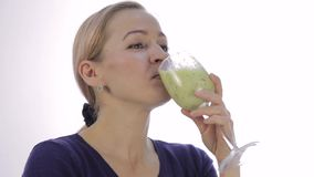 白肤金发的女孩喝绿色戒毒所鸡尾酒 健身和健康生活方式的菜圆滑的人 股票视频