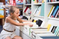 白肤金发的女孩在图书馆里选择一本书 免版税图库摄影