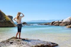 白肤金发的女孩在多岩石的海滩站立 免版税库存图片