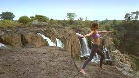 白肤金发的女孩在岩石的瑜伽姿势站立在瀑布附近 股票录像