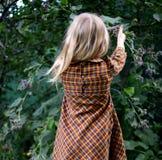 白肤金发的女孩在庭院里走! 免版税库存照片