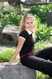 白肤金发的女孩在庭院里 免版税库存照片