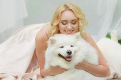 白肤金发的女孩在手上说谎户外与一条白色狗 免版税库存照片