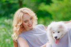 白肤金发的女孩在手上说谎户外与一条白色狗 免版税库存图片
