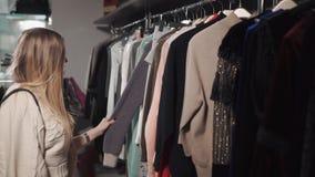 白肤金发的女孩在时髦商店看在挂衣架的衣裳 影视素材