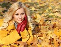 白肤金发的女孩在有槭树的秋天公园离开。时尚 库存照片