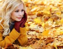 白肤金发的女孩在有槭树的秋天公园离开。美好的时尚 免版税库存图片